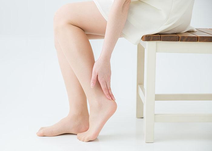 座りながら足を触る女性
